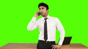 Young businessman talking on mobile phone against green background stock video footage