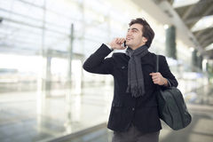 Young businessman talking on mobile phone in airport Stock Images