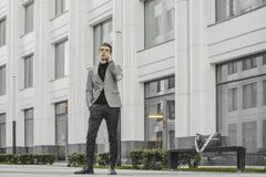 Young businessman talking by mobile phone next to business center. royalty free stock photos