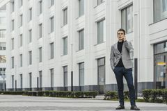 Young businessman talking by mobile phone next to business center. stock photography