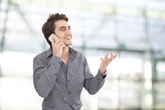 Young businessman talking mobile phone in the office Royalty Free Stock Images