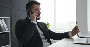 Businessman talking on mobile phone. Young businessman talking on mobile phone at office stock video