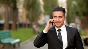 Young businessman talking on mobile phone. Outdoors stock video