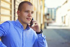 Young businessman talking on mobile phone on street Stock Photo