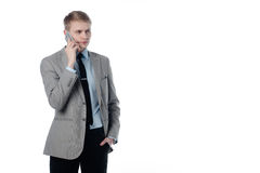 Young businessman talking on the phone. In a business suit on a white background Stock Image