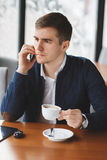 Young businessman talking on the phone in cafe Royalty Free Stock Photos