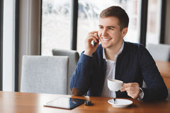 Young businessman talking on the phone in cafe Stock Image