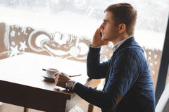 Young businessman talking on the phone in cafe Stock Photos