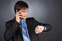 Young businessman talking on phone while looking at his watch Stock Photos
