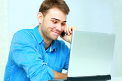 Young businessman talking on the phone and looking on laptop Stock Image