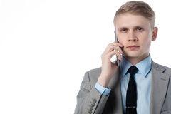 Young businessman talking on the phone and looks at you. In a business suit on a white background Stock Image