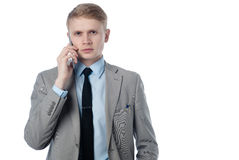 Young businessman talking on the phone and looks at you. In a business suit on a white background Royalty Free Stock Photo