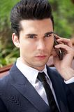 Young businessman talking on phone outside the office. Close up portrait of a young businessman talking on the phone outside the office Royalty Free Stock Images