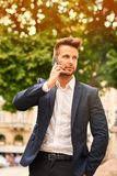 Young businessman talking on a phone on the sunny street stock photo