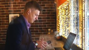A young businessman talking on the phone and working at a laptop in a cafe. Young businessman working on laptop computer in store stock footage