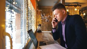 A young businessman talking on the phone and working at a laptop in a cafe. Young businessman working on laptop computer in store stock video footage