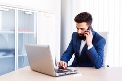 Young Businessman Talking On Phone While Works On Laptop. Young Business Man Working On Laptop At Office - Workplace Royalty Free Stock Image