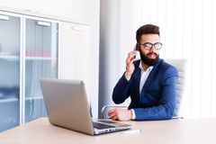 Young Businessman Talking On Phone While Works On Laptop. Young Business Man Working On Laptop At Office - Workplace Stock Photos