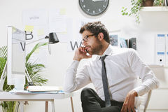 Young businessman talking on smartphone in office, Royalty Free Stock Image