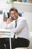 Young businessman talking on smartphone in office. Royalty Free Stock Photo