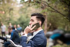 Young businessman talking on smartphone outdoors in the park. A young and attractive businessman talking on his smartphone outdoors in the park Stock Photo