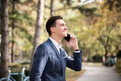 Young businessman talking on smartphone outdoors in a park. A young elegant businessman talking on smartphone outdoors in a park, happy, positive conversation Stock Photo