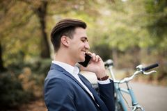 Young businessman talking on smartphone outdoors in a park. A young businessman talking on his smartphone outdoors in a park, sitting on a bench Royalty Free Stock Images