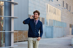 Young businessman talking smartphone walking Stock Images