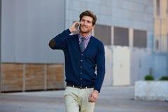 Young businessman talking smartphone walking Stock Photos