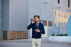 Young businessman talking smartphone walking Royalty Free Stock Photos
