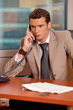 Young businessman talking on telephone in office Stock Images