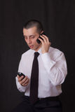 Young businessman talking on two phones stock images