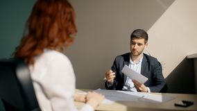 Young businessman talking with woman, holding documents sitting at table in company. Young businessman talking with woman, holding documents sitting at table in stock video