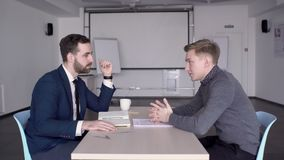 Young businessman is in talks with employee in modern office. Two men communicate while sitting at table in leading company indoors. Confident boss is at desk stock footage