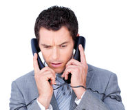 Young businessman tangle up in phone wires Stock Photography