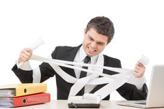 Young businessman tearing paper apart. Royalty Free Stock Image