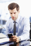 Young businessman text messaging on cellphone Royalty Free Stock Photo