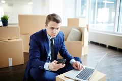 After relocation. Young businessman texting in smartphone while ordering food online after relocation to new office Stock Image