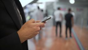 Young businessman texting on smartphone while standing in queue, modern gadgets stock footage