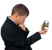Young businessman thinking about... Young business man holding an alarmclock and thinking about something Stock Image