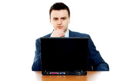 Young businessman thinking behind the computer. (focus on computer Royalty Free Stock Photo