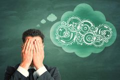 Businessman thinking about cogs. Young businessman thinking about cogs on chalkboard background. Industry and mechanism concept stock photography