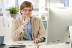 Young businessman thinking at desk Stock Images