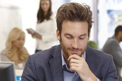 Young businessman thinking in office Royalty Free Stock Image