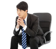 Young businessman thinking and sitting in a chair Stock Photo