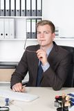 Young businessman is thoughtfully sitting at the desk Stock Photo