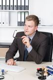 Young businessman is thoughtfully sitting at the desk Royalty Free Stock Photography
