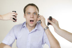 Young businessman and three cellphones Royalty Free Stock Image