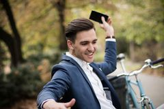 Young businessman throwing away his smartphone in the park. A young and attractive businessman throwing away his smartphone in the park, feeling surprised royalty free stock images