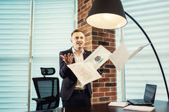 Young businessman throwing some paper sheets in the air,business. People, stress, emotions and fail concept - angry businessman throwing papers in office stock image